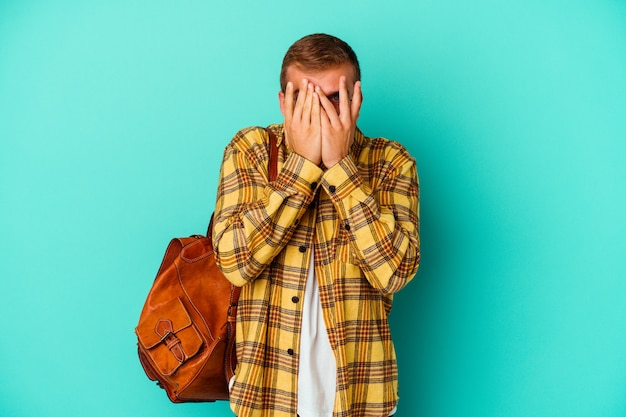 두려워 하 고 긴장하는 손가락을 통해 파란색 깜박임에 고립 된 젊은 백인 학생 남자.