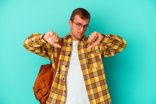 親指を下に向けて嫌悪感を表現している青い壁に孤立した若い白人学生の男。