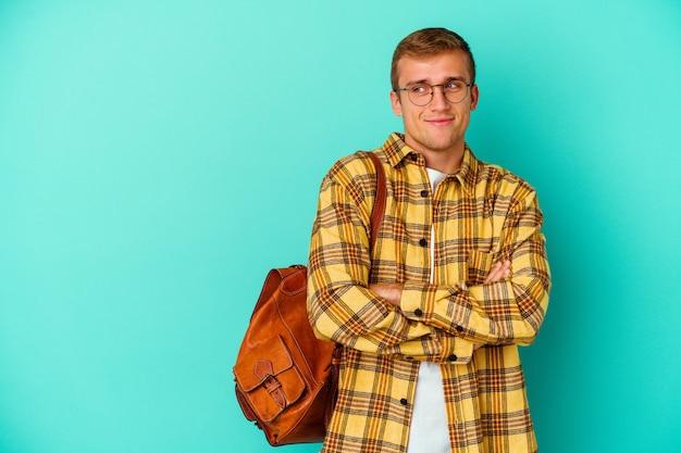 파란색 벽 교차 팔 자신감 웃 고에 고립 된 젊은 백인 학생 남자.