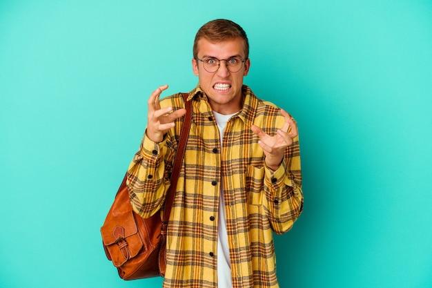 青い壁に孤立した若い白人学生の男は、緊張した手で叫んで動揺しました。