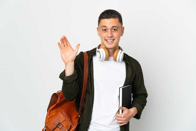 Young caucasian student man isolated on white background saluting with hand with happy expression