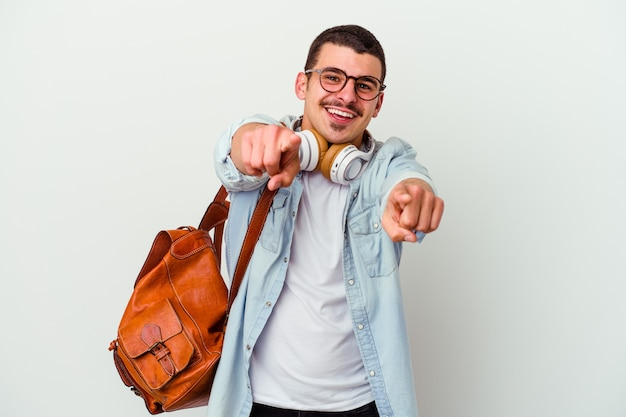Young caucasian student man listening to music isolated on white background cheerful smiles pointing to front.