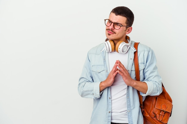 Young caucasian student man listening to music isolated on white background making up plan in mind, setting up an idea.