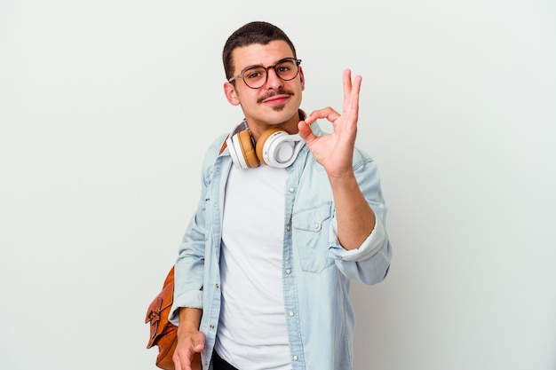 Young caucasian student man listening to music isolated on white wall cheerful and confident showing ok gesture.