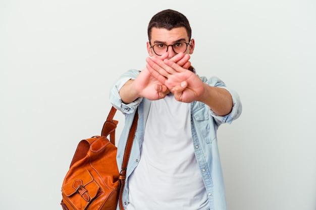 Молодой кавказский студент человек слушает музыку на белом фоне, делая жест отрицания