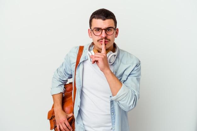 秘密を守るか、沈黙を求めて白い背景で隔離の音楽を聞いている若い白人学生の男。