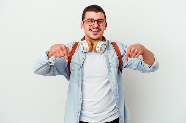白い背景で隔離の音楽を聴いている若い白人学生の男は、指で下向き、前向きな気持ち。