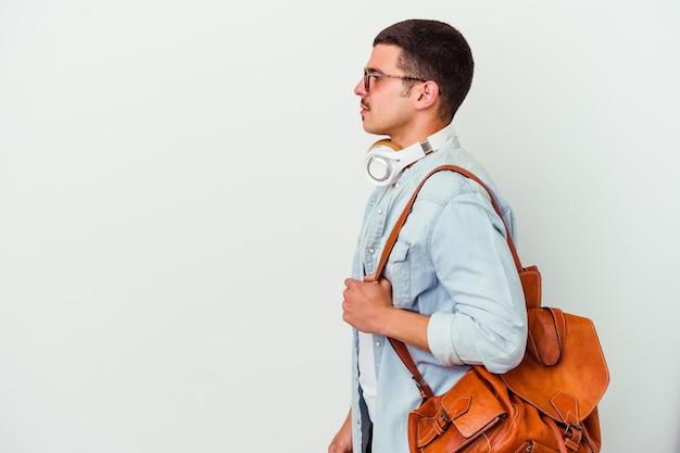 左、横向きのポーズを見つめている白い壁に分離された音楽を聴いている若い白人学生の男