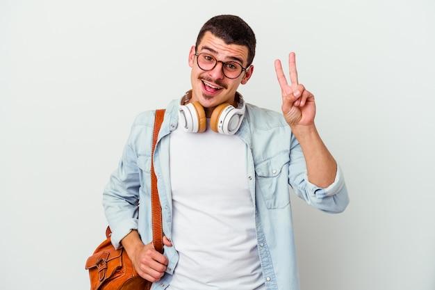 白い壁に隔離された音楽を聞いている若い白人学生の男性は、指で平和のシンボルを示して楽しくてのんきです。