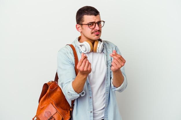 Молодой человек кавказского студента слушает музыку изолированную на белой стене показывая, что у нее нет денег.
