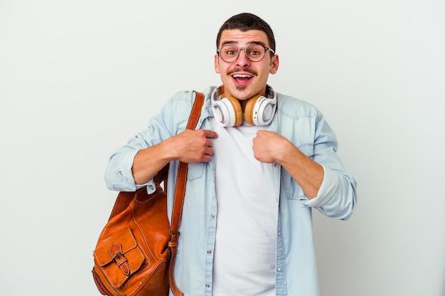 白い壁に隔離された音楽を聞いている若い白人学生の男は、指で指して、広く笑って驚いた
