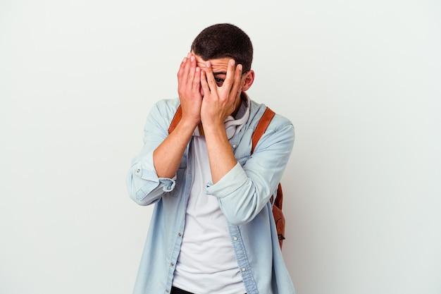 Молодой кавказский студент, слушающий музыку на белом, мигает сквозь пальцы, испуганный и нервный.