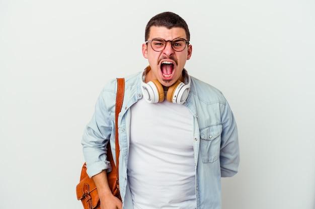 Молодой кавказский студент человек слушает музыку на белом кричит очень сердито и агрессивно.