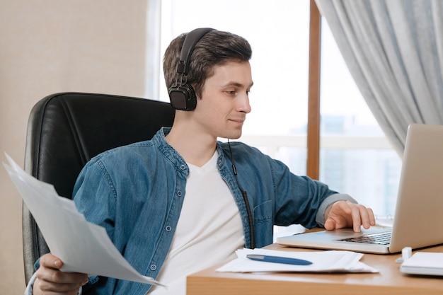 遠隔教育のためにラップトップを使用し、彼の部屋に座って、講義を聞いて、ヘッドフォンを持っている若い白人学生がオンラインでレッスンをしています