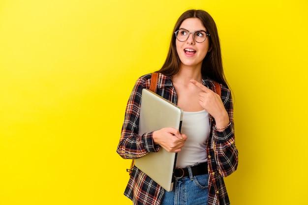 멀리 엄지 손가락으로 분홍색 벽 점에 고립 된 노트북을 들고 젊은 백인 학생 여자, 웃음과 평온한