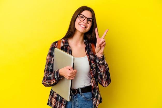 ピンクの壁に隔離されたラップトップを持っている若い白人学生の女性は、指で2番目を示しています。