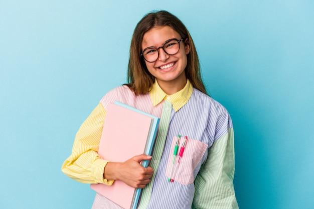 행복 하 고 웃 고 쾌활 한 파란색 배경에 고립 된 책을 들고 젊은 백인 학생 여자.