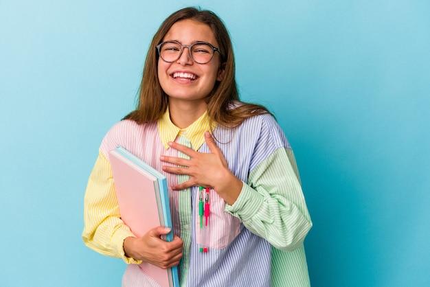 青い背景で隔離の本を持っている若い白人学生の女性は胸に手を置いて大声で笑います。