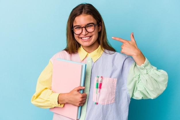 シャツのコピースペースを手で指している青い背景の人に分離された本を保持している若い白人学生女性、誇りと自信を持って