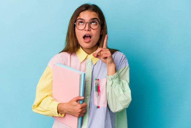 열린 된 입으로 거꾸로 가리키는 파란색 배경에 고립 된 책을 들고 젊은 백인 학생 여자.