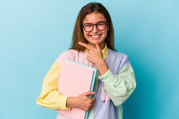 웃 고 옆으로 가리키는 파란색 배경에 고립 된 책을 들고 젊은 백인 학생 여자 빈 공간에서 뭔가 보여주는.