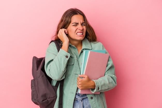 手で耳を覆うピンクの背景に分離された本を保持している若い白人学生女性。