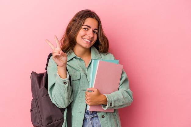 指で2番目を示すピンクの背景に分離された本を保持している若い白人学生の女性。