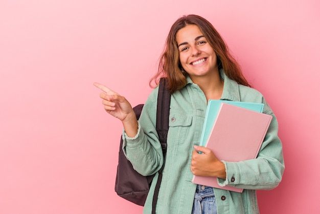 ピンクの背景に分離された本を持っている若い白人学生の女性は、笑顔で脇を指して、空白のスペースで何かを示しています。