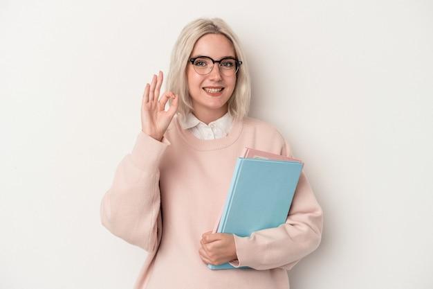白い背景で隔離の本を持っている若い白人学生の女性は陽気で自信を持って大丈夫なジェスチャーを示しています。