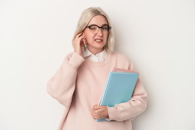 手で耳を覆う白い背景で隔離の本を保持している若い白人学生女性。