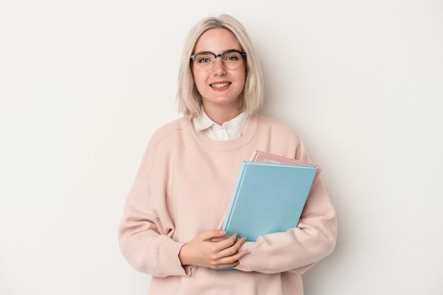 幸せ、笑顔、陽気な白い背景で隔離の本を保持している若い白人学生の女性。