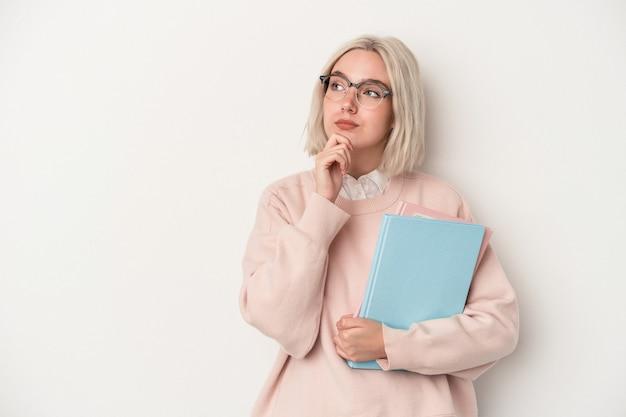 疑わしいと懐疑的な表現で横向きに白い背景で隔離の本を保持している若い白人学生の女性。