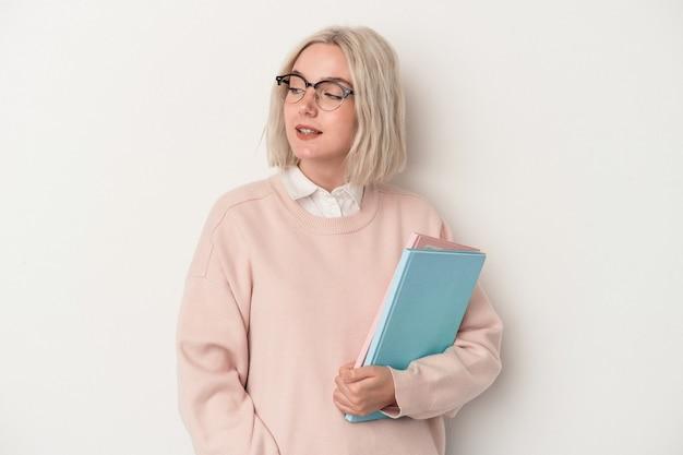白い背景で隔離の本を保持している若い白人学生の女性は、笑顔、陽気で楽しい脇に見えます。
