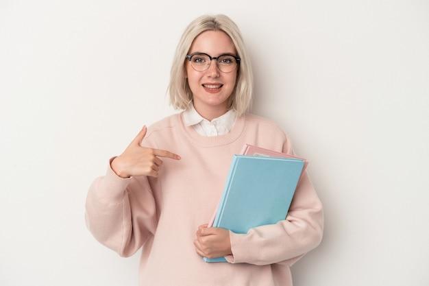 シャツのコピースペースを手で指している白い背景の人に分離された本を保持している若い白人学生女性、誇りと自信を持って