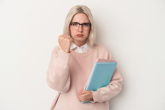 カメラに拳、積極的な表情を示す白い背景で隔離の本を保持している若い白人学生の女性。