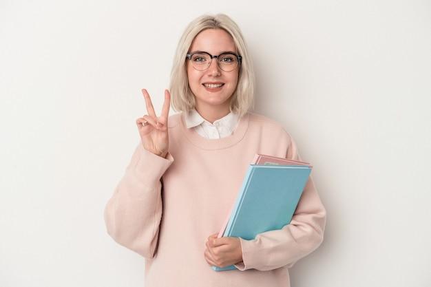 指で2番目を示す白い背景で隔離の本を保持している若い白人学生の女性。