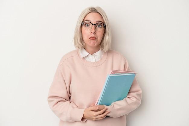 白い背景で隔離の本を保持している若い白人学生の女性は肩をすくめ、目を開けて混乱します。