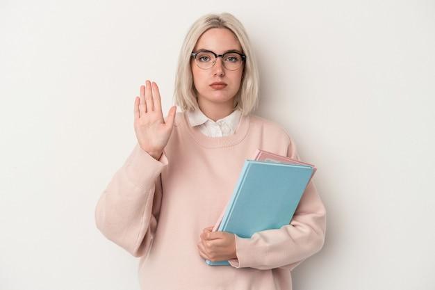 흰색 배경에 격리된 책을 들고 있는 젊은 백인 학생 여성은 뻗은 손으로 정지 신호를 표시하고 당신을 방해합니다.