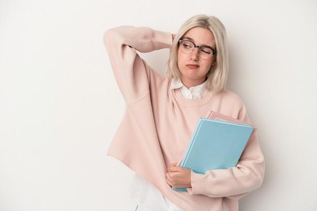 頭の後ろに触れて、考えて、選択をする白い背景で隔離の本を保持している若い白人学生の女性。