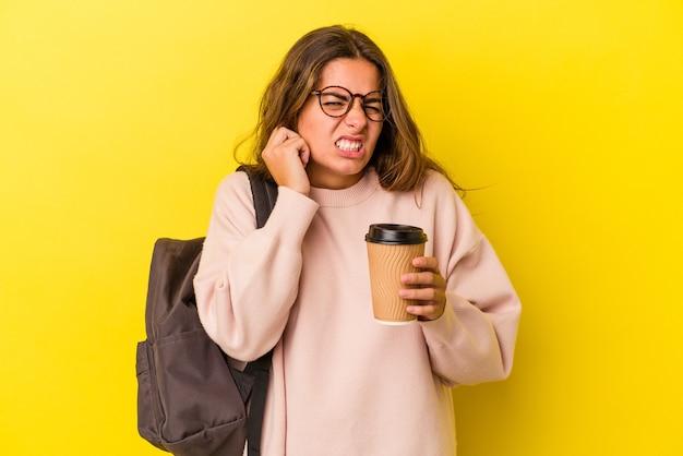 手で耳を覆う黄色の背景に分離されたコーヒーを保持している若い白人学生女性。
