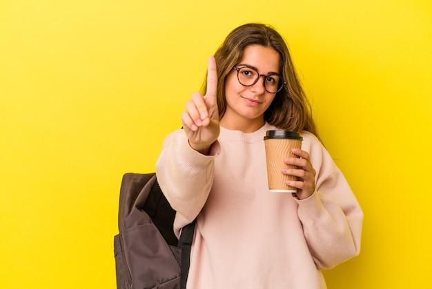 指でナンバーワンを示す黄色の背景に分離されたコーヒーを保持している若い白人学生の女性。