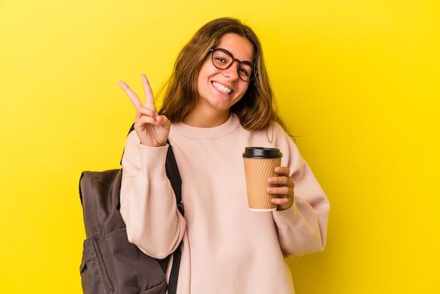 指で2番目を示す黄色の背景に分離されたコーヒーを保持している若い白人学生の女性。