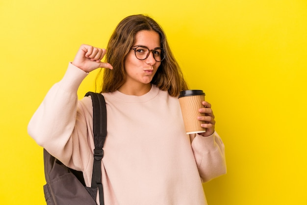 Young caucasian student woman holding coffee isolated on yellow background  feels proud and self confident, example to follow.