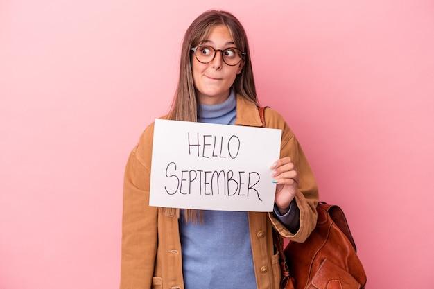 ピンクの背景に分離されたこんにちは9月のプラカードを保持している若い白人学生の女性は混乱し、疑わしく、不安を感じています。