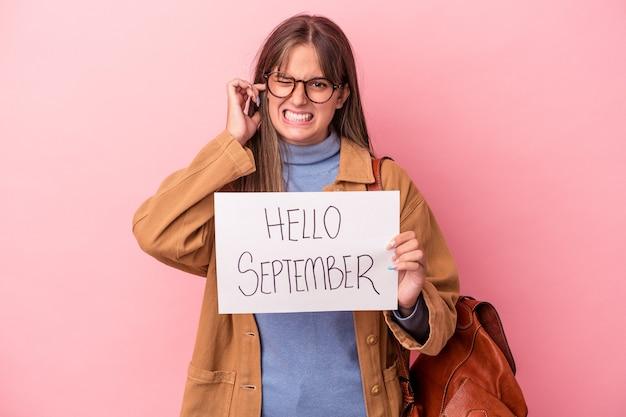 手で耳を覆うピンクの背景に分離されたこんにちは9月のプラカードを保持している若い白人学生の女性。