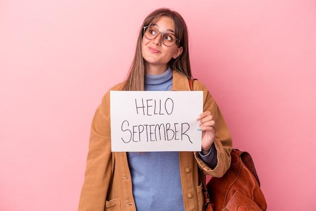 目標と目的を達成することを夢見ているピンクの背景に分離されたこんにちは9月のプラカードを保持している若い白人学生の女性