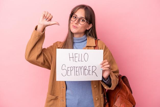 ピンクの背景に分離されたこんにちは9月のプラカードを保持している若い白人学生の女性は、誇りと自信を感じています。