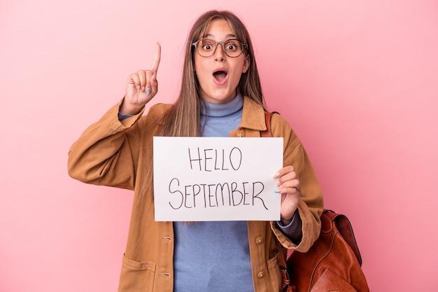 アイデア、インスピレーションのコンセプトを持つピンクの背景に分離されたこんにちは9月のプラカードを保持している若い白人学生の女性。