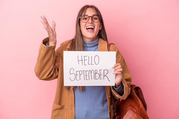 ピンクの背景に分離されたこんにちは9月のプラカードを保持している若い白人学生の女性は、嬉しい驚きを受け取り、興奮し、手を上げます。