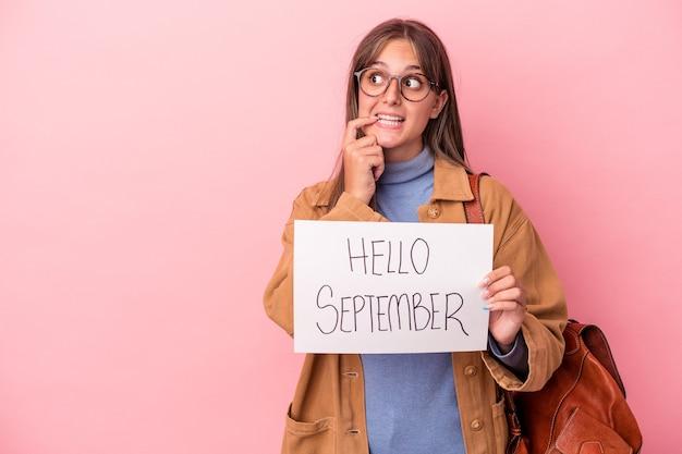ピンクの背景に分離されたこんにちは9月のプラカードを保持している若い白人学生の女性は、コピースペースを見ている何かについて考えてリラックスしました。